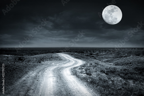 Poster de jardin Gris Empty rural road going through prairie at full moon night with dramatic cloudy sky