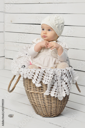 8d4df76cd Cute baby girl sitting in a basket in a knitted hat. - Buy this ...