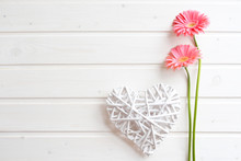 Two Pink Gerber Daisy Flowers On  Wooden Backgraund. Gerbera And Decorative Heart. Flat Lay, Top View