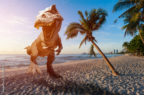 Fototapeta Dinosaur model on the beach in the morning obraz