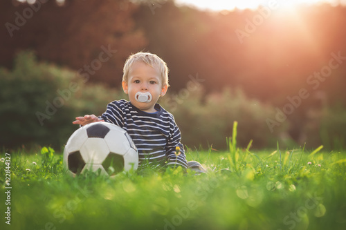 Photo  Toddler playing with a soccer ball in the sunset