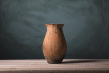 Red Ornamental Clay Pot/Pottery Vase Made Of Clay And Painted In Red Against A Green Background
