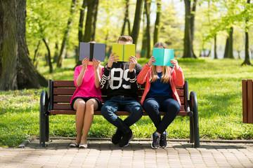 Czytanie książek w parku przez wesołą młodzież szkolną. Wygłupy przy czytaniu.