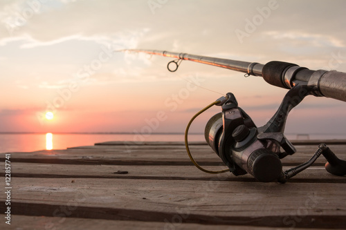 Fényképezés  Fishing reel and rod lying on wooden pier over the sunset lake