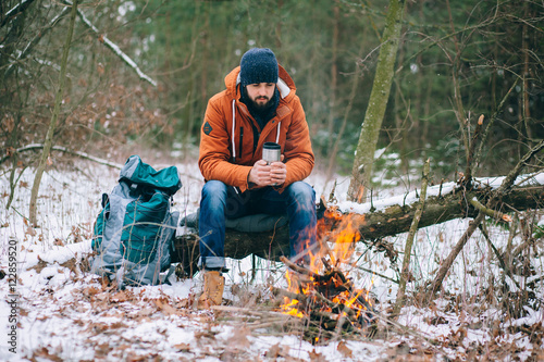 Egypt hiker warming hands at campfire in winter forest