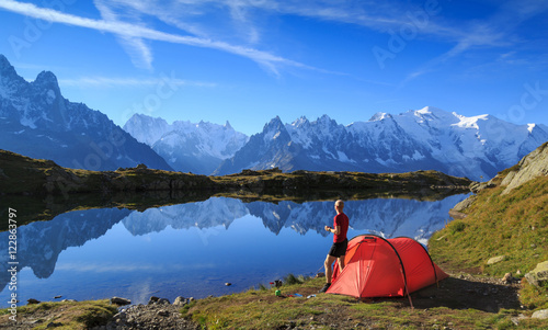 Poster de jardin Camping Hiker enjying the view at his red tent in the mountains near Chamonix, France.