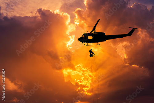 Foto op Aluminium Helicopter silhouette soldiers in action rappelling climb down with military mission counter terrorism assault training on sunset background