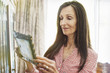 Smiling senior woman with long brown hair holding a picture frame, looking at a picture.
