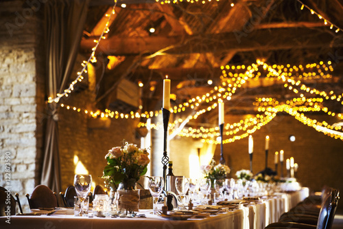 A wedding venue decorated for a party, with fairy lights and the tables set for dinner.