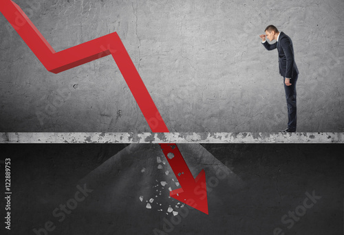 Photo Businessman looking down at the falling red arrow destroying a concrete barrier