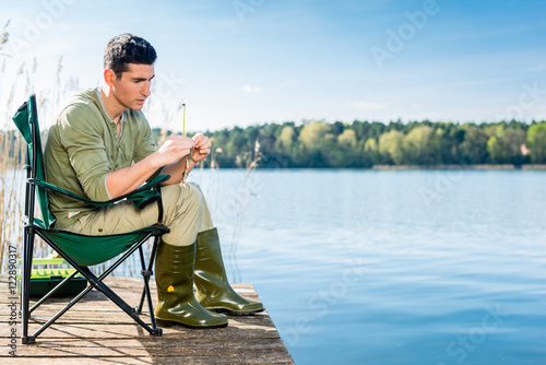 Fotobehang Vissen Man fishing at lake fixing lure at angling rod