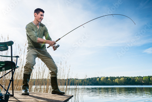 Foto op Canvas Vissen Fisherman catching fish angling at the lake