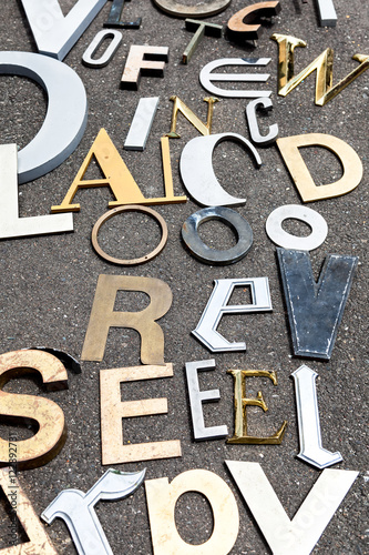 vintage metal letters in various fonts and sizes on concrete background