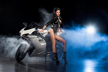 Obraz na płótnie Canvas Piękna seksowna dziewczyna w skórzanej kurtce stoi przy motocyklu