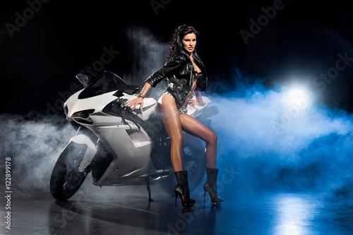 Fototapeta Piękna seksowna dziewczyna w skórzanej kurtce stoi przy motocyklu obraz