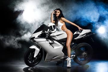 Obraz na płótnie Canvas Piękna seksowna dziewczyna w białym stroju siedzi na białym motocyklu