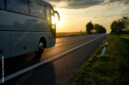Zdjęcie XXL Biały autobus jazdy wzdłuż drogi asfaltowej w wiejski krajobraz o zachodzie słońca.