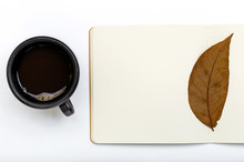 Open Notepad With One Autumn Leaf And Cup Of Coffee.