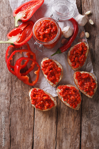Foto op Canvas Klaar gerecht Ajvar - delicious dish of red peppers, onions and garlic closeup. Vertical top view
