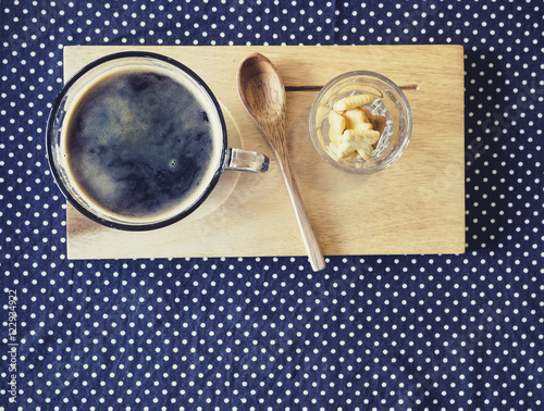 Obraz w ramie Cup of coffee on wooden tray wooden spoon with crackers Vintage tone