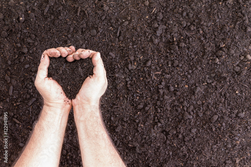 Pair of hands holding soil in heart shape Wallpaper Mural