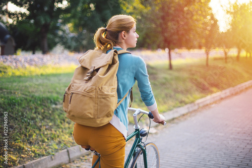 Aluminium Prints Cycling Young woman with backpack cycling in the park