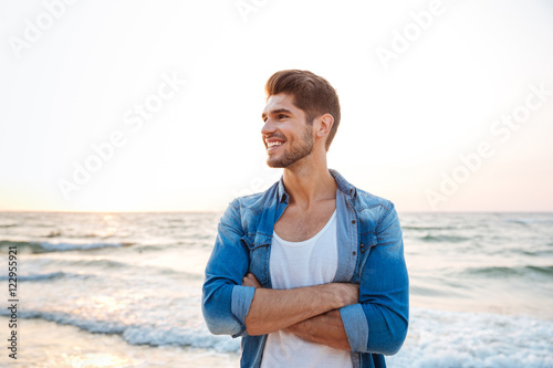 Photographie  Cheerful young man standing with hands crossed on the beach