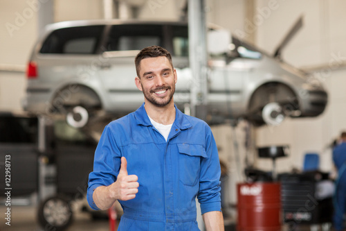 happy auto mechanic man or smith at car workshop