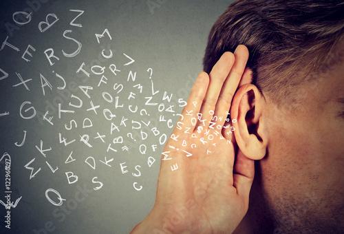 Fotografía man holds hand near ear listens carefully alphabet letters flying in