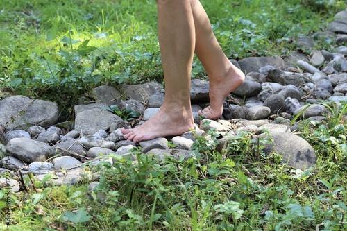 Photo woman walking barefoot on a stony way