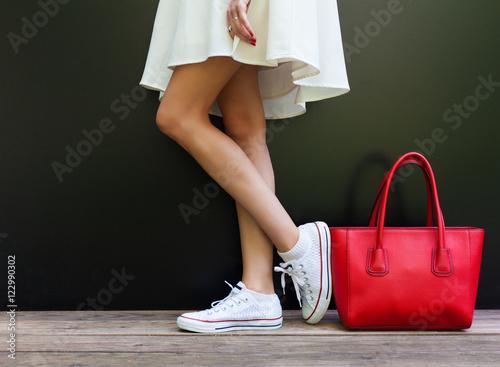 Fotografia  beautiful fashionable big red handbag standing next to leggy woman in white shor