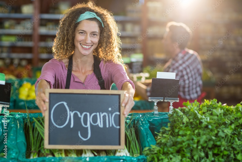 Fototapety, obrazy: Smiling staff holding organic sign board in organic section