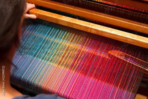 Fotografiet  Woman's hands on the color warp
