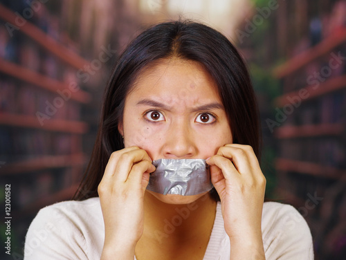 Young Brunette Woman Wearing White Sweater Gagged With Duct Tape Covering Mouth Facing Camera