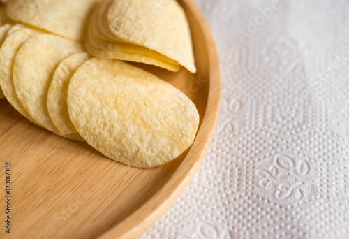 Garden Poster Spa Fried crispy potatoes chips on round wood plate background