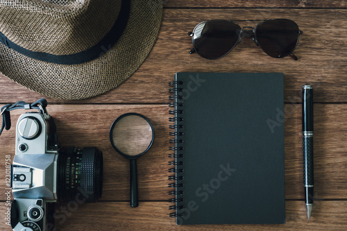 Fotografie, Tablou  Black notebook with copyspace and retro camera on wooden backgrond