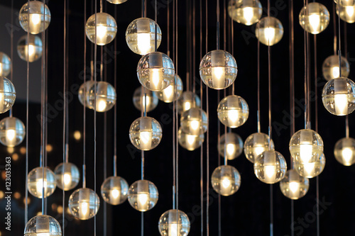 Fotomural lighting balls on the chandelier in the lamplight,  light bulbs hanging from the ceiling, lamps on the dark background, selective focus, horizontal