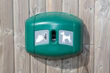 Green Dog Waste Station Under Wooden Background