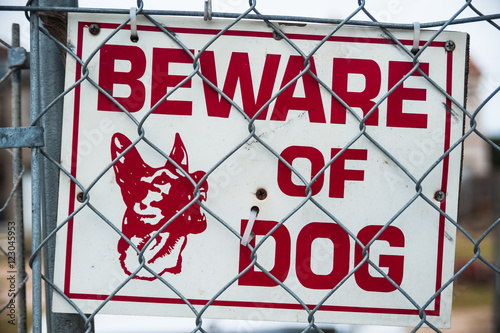Fotografie, Obraz  beware of guard dog sign on chain link fence