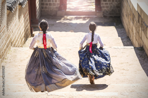 Two Korean Girls dressed in traditional dress running down stairs in Seoul stree Poster