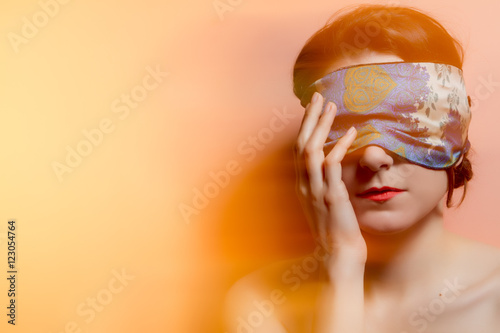 Fotografie, Obraz  Portrait of a woman with covered eyes in rays of light. Techniqu