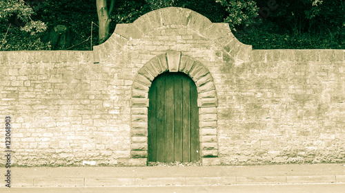 Valokuva  Old Wooden Door with Stone Round Arch