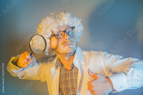 Photo  funny scientist, like Einstein with a magnifying glass