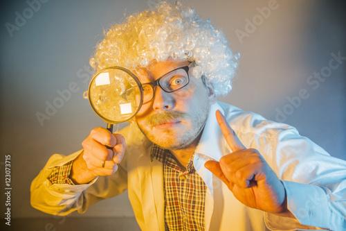 Foto  Lustiger Wissenschaftler, wie Einstein mit einer Lupe