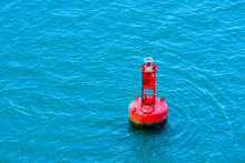 A Bright Red Buoy Floating In A Blue Ocean