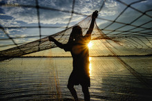 Silhouette Fisherman Casting The Net At The Lake In Thailand