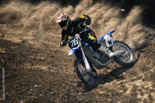 Motocross jeźdźca tworzy dużą chmurę pyłu i gruzu