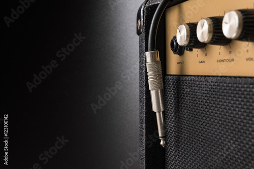Black guitar amplifier with jack cable on black background Wallpaper Mural