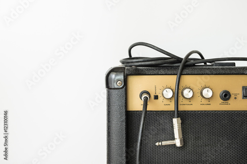 Foto Black guitar amplifier with jack cable on white background
