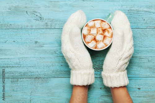 Spoed Foto op Canvas Chocolade Woman hands in mittens hold cup of hot cocoa or chocolate with marshmallow on turquoise vintage table from above. Flat lay style.